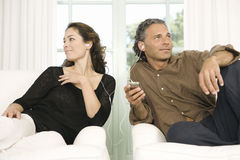 Mature couple sharing headphones. Mature couple sharing earphones while listening to music with an mp4 in their home's living room Stock Photos