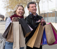 Mature couple with shopping bags in autumn day. Happy mature couple with shopping bags in autumn day Royalty Free Stock Images