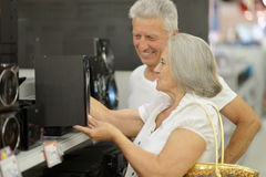 Mature couple on shopping. Choosing audio system Royalty Free Stock Photos