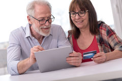 Mature couple shopping online with tablet and credit card Stock Photos