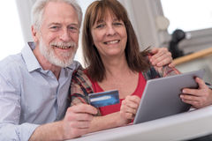 Mature couple shopping online with tablet and credit card Royalty Free Stock Photography