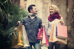 Mature couple in shopping tour. Portrait of happy mature couple chasing streets in shopping tour Stock Image