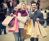 Mature couple in shopping tour. Portrait of smiling mature couple with shopping bags at streets stock photo