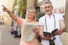 Mature couple sightseeing. Mature tourist sightseeing city with map and guidebook Stock Photos