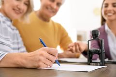 Mature couple signing document in notary`s office