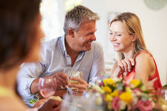 Mature Couple Sitting Around Table At Dinner Party Stock Image