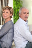 Mature couple sitting back to back Stock Photos
