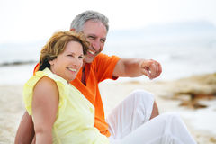 Mature couple sitting on the beach. Stock Photography