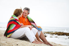 Mature couple sitting on the beach. royalty free stock photography