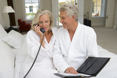 Mature couple sitting on bed, man smiling at woman talking on telephone Stock Photo