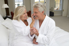 Mature couple sitting on bed, woman holding mobile phone by man's ear, smiling Stock Image