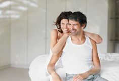 Mature couple sitting in bedroom and looking away Royalty Free Stock Images