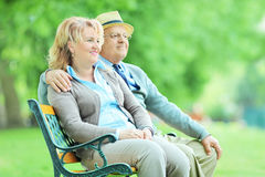 Mature couple sitting on a bench in park Stock Image
