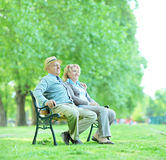 Mature couple sitting on a bench in park Royalty Free Stock Photo