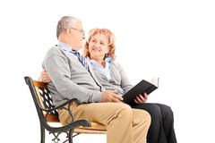 Mature couple sitting on a bench and reading book Stock Image