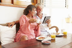 Mature Couple Sitting At Breakfast Table With Digital Tablet Stock Photo