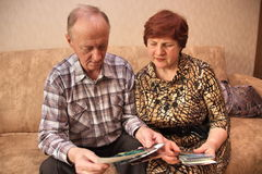 Mature couple sitting on the couch. And looking at pictures Stock Images