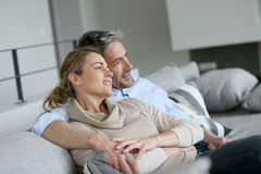 Mature couple sitting on couch embracing Stock Photography