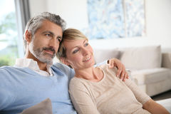 Mature couple sitting on couch Stock Photos