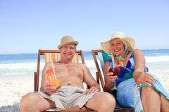 Mature couple sitting on deck chairs Royalty Free Stock Photos