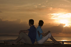 Mature couple sitting in front of sunrise Royalty Free Stock Photos