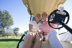 Mature couple sitting in golf buggy on golf course, man driving, smiling, front view, low angle view Stock Photography