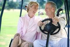 Mature couple sitting in golf buggy on golf course, man driving, smiling, front view Stock Photography
