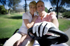 Mature couple sitting in golf buggy on golf course, man driving, woman embracing man, smiling, front view, portrait, focus on golf Royalty Free Stock Photos