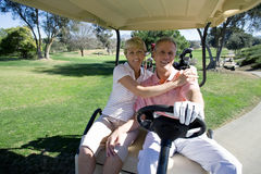 Mature couple sitting in golf buggy on golf course, man driving, woman embracing man, smiling, front view, portrait Royalty Free Stock Photo