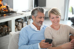 Mature couple sitting at home by fireplace Stock Images