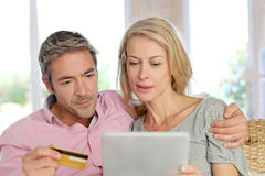 Mature couple sitting at home using credit card for shopping Stock Photo