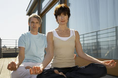 Mature couple sitting in a lotus position Stock Photos