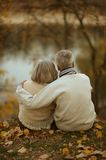 Mature couple sitting near lake Stock Photos