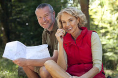 A mature couple sitting outdoors resting, man holding a map Royalty Free Stock Photo