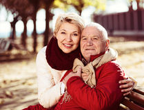 Mature couple sitting in park. Aged husband and wife sitting together on bench in park on chilly day royalty free stock photo