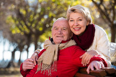 Mature couple sitting in park. Aged husband and wife sitting together on bench in park on chilly day stock image