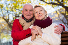 Mature couple sitting in park. Aged husband and wife sitting together on bench in park on chilly day royalty free stock image