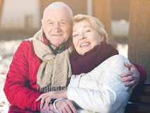 Mature couple sitting in park. Senior couple sitting on bench and embracing in park royalty free stock images