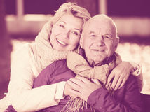 Mature couple sitting in park. Senior couple sitting on bench and embracing in park stock image