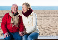Mature couple sitting by sea Royalty Free Stock Photography