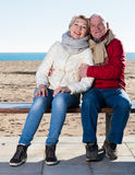 Mature couple sitting by sea. Aged husband and wife sitting together on bench by sea on chilly day stock photos
