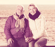 Mature couple sitting by sea Stock Photography