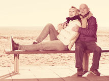 Mature couple sitting by sea Stock Photo