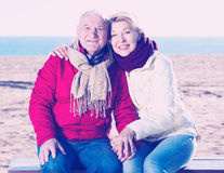 Mature couple sitting by sea Stock Photos