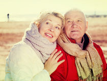 Mature couple sitting by sea Stock Image