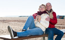 Mature couple sitting by sea Stock Photo