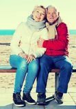 Mature couple sitting by sea Stock Images