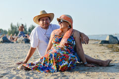 Mature couple sitting at seashore on summer sandy beach outdoors background. Happy smiling & looking at camera mature couple sitting at seashore on sandy beach Royalty Free Stock Images
