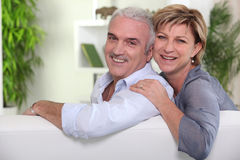 Mature couple sitting on sofa Stock Image