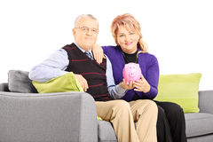Mature couple sitting on a sofa and holding a piggy bank Stock Image